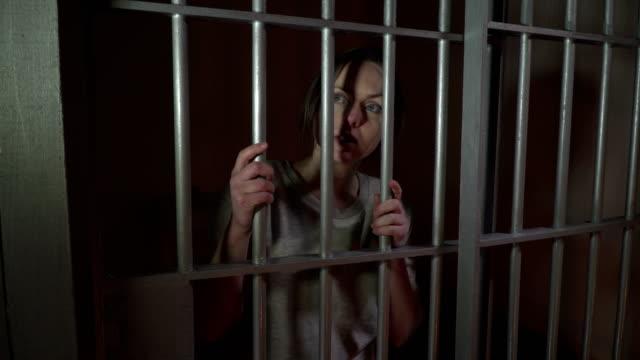 4K Female Prisoner in Jail holding the bars