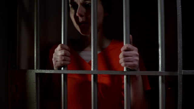 4K DOLLY: Female Prisoner in Jail holding the bars