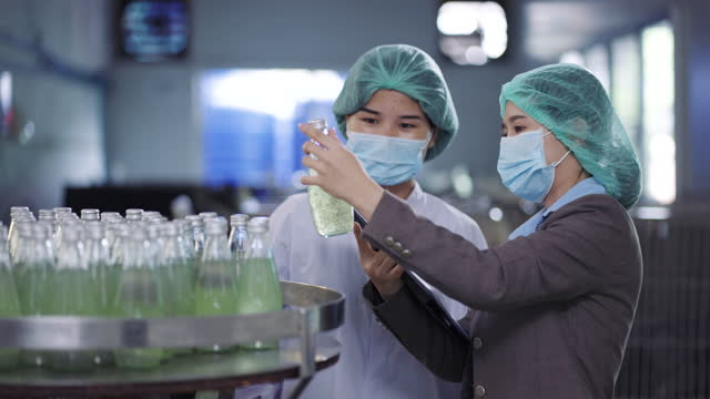 female production line workers inspecting the juice bottle product - bottling plant stock videos & royalty-free footage