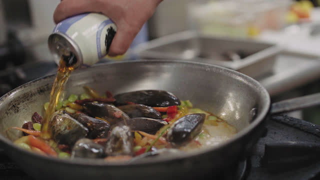 female professional chef adds a can of ale to a pan of fresh mussels cooking on a commercial kitchen stove top - equality stock videos & royalty-free footage