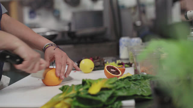 female professional chef slices blood oranges on a cutting board in a commercial kitchen next to an herb garden - incentive stock videos & royalty-free footage