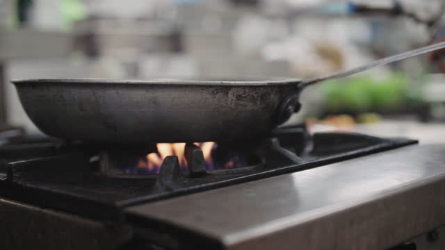 cu. female professional chef uses a kitchen torch to light a gas stove burner on a commercial kitchen stove top and adds oil to the pan - burner stove top stock videos and b-roll footage