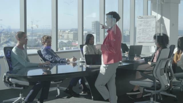 vidéos et rushes de female professional planning with team at office - table de salle de réunion
