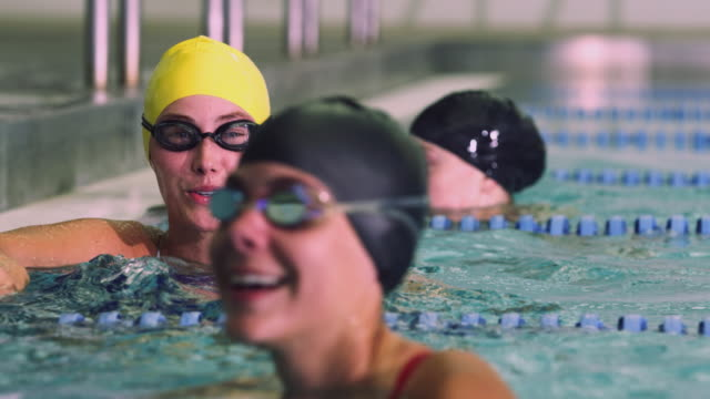 female professional swimmer smiles at her competitors at the end of the swimming lane after celebrating her win during a swim meet in an indoor olympic sized swimming pool - swimming goggles stock videos & royalty-free footage