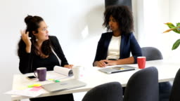 Female professionals discussing at desk in office