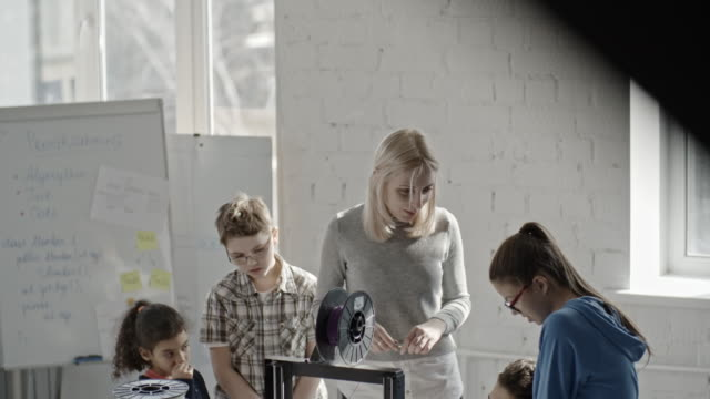 Female programmer showing 3D printer to school children