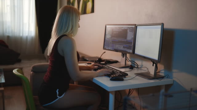 vídeos de stock e filmes b-roll de female programmer writes code looking at two monitors at home - dois objetos