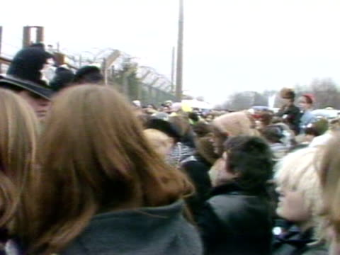 female protestors crowd into police who are guarding the perimeter fence of greenham common airbase. - fence stock videos & royalty-free footage