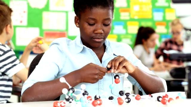 Female Pupil Using Molecular Model Kit In Science Lesson