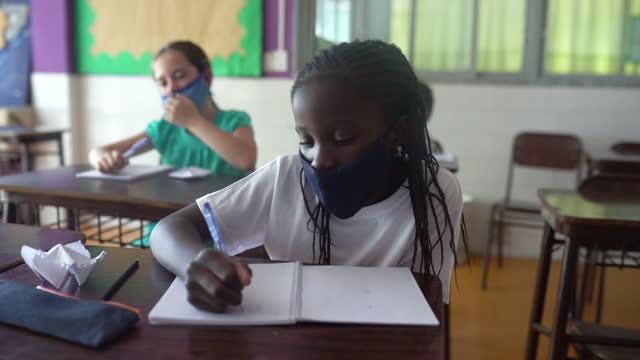 教室で授業をしている女子生徒。コーヴィッド-19 コンセプト - 消しゴム点の映像素材/bロール