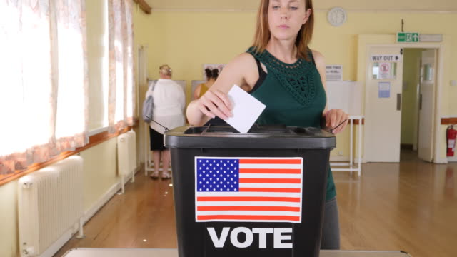4k: female puts vote in ballot box at the usa election - voting at polling place - voting booth stock videos and b-roll footage