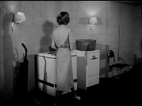 female putting clothes into washing machine in basement. vs various appliances, including lamp, vacuum cleaner. female sitting down to dry machine... - housework stock videos & royalty-free footage