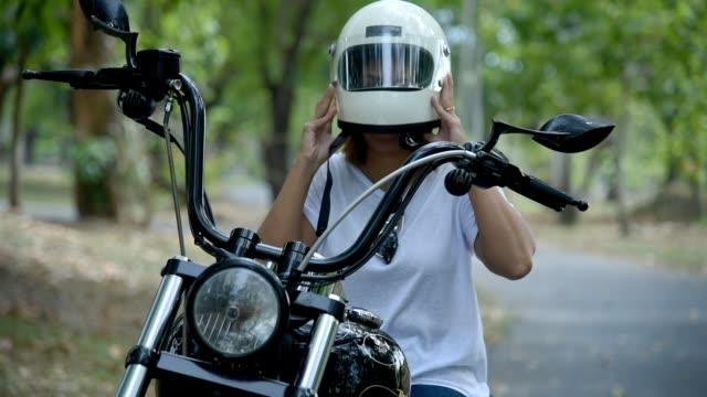 Female putting on helmet on her chopper motorcycle.