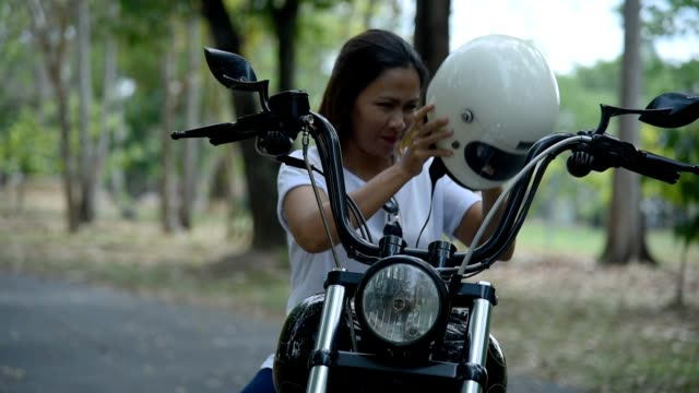 vidéos et rushes de femelle mettant sur le casque sur sa moto d'hélicoptère. - casque de moto
