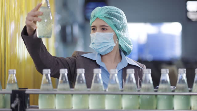 female quality inspectors standing near the production line inspecting the final product - surgical cap stock videos & royalty-free footage
