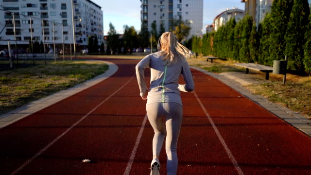 female race runner listening to music - pista di atletica leggera video stock e b–roll