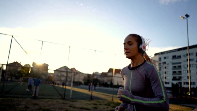 female race runner listening to music - dedication stock videos & royalty-free footage