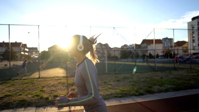 vídeos y material grabado en eventos de stock de corredora de carreras femenina escuchando música - auriculares equipo de música