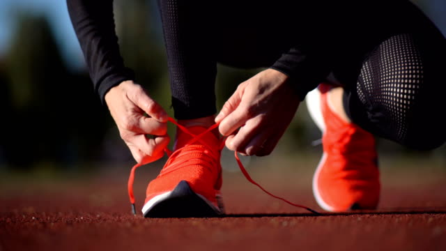 female race runner tying shoelaces - tie stock videos & royalty-free footage