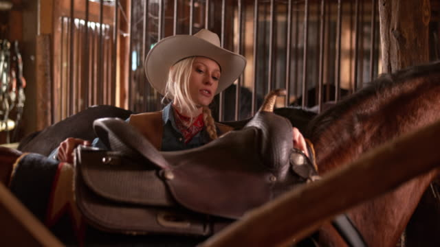 DS Female rancher putting a saddle on her horse