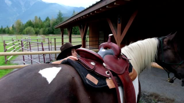 female rancher saddles her horse - rancher stock videos & royalty-free footage