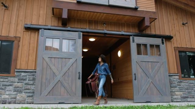 vídeos de stock, filmes e b-roll de o rancheiro fêmea anda com uma sela - cavalgar