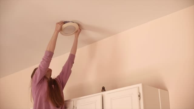 female reaches up to install recessed light fixture - chores stock videos & royalty-free footage