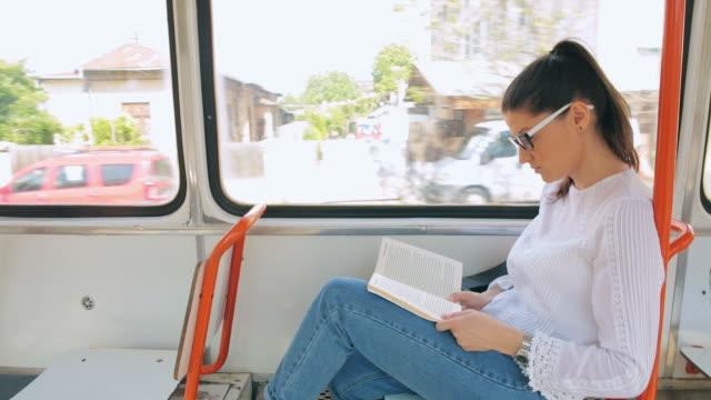 weibliche beim buchlesen in die straßenbahn ein. - öffentliches verkehrsmittel stock-videos und b-roll-filmmaterial
