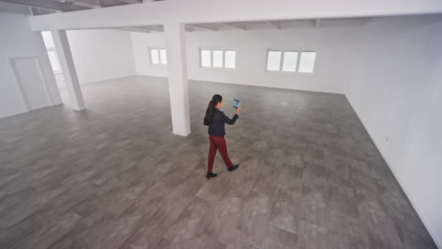 vidéos et rushes de cs agent immobilier féminin ayant un appel vidéo avec les clients leur montrant un espace de bureau vide - immobilier