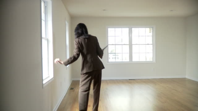 WS, PAN, Female real estate agent in empty room, Plainfield, New Jersey, USA