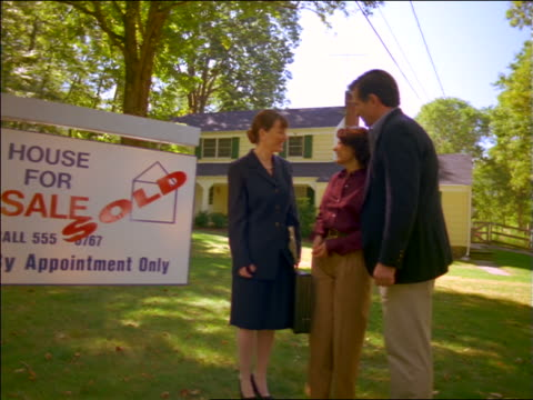 """female real estate agent shaking hands with couple on lawn outside of house / """"sold"""" sign in foreground - estate agent sign stock videos & royalty-free footage"""