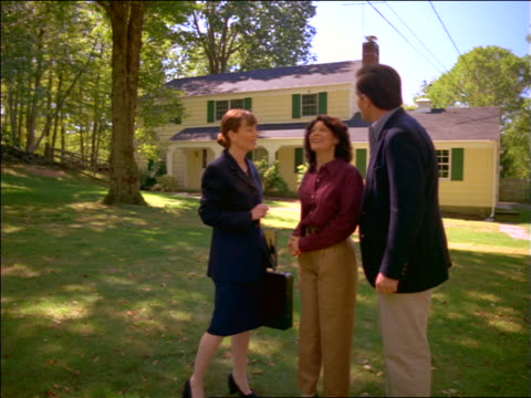 Female real estate agent showing house + grounds to couple