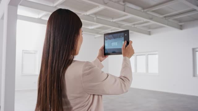 vidéos et rushes de agent immobilier féminin prenant des photos d'un bâtiment d'affaires vide utilisant une tablette numérique - immobilier