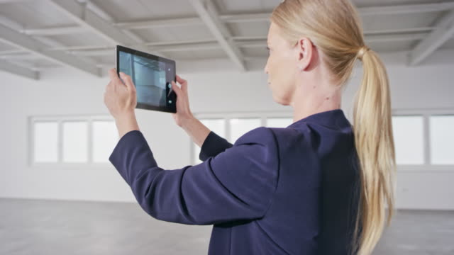 female real estate agent taking photos of an office space in an empty business building using a digital tablet - ponytail stock videos & royalty-free footage