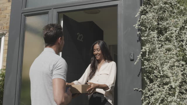 female receiving package at front door from delivery person - building entrance stock videos & royalty-free footage