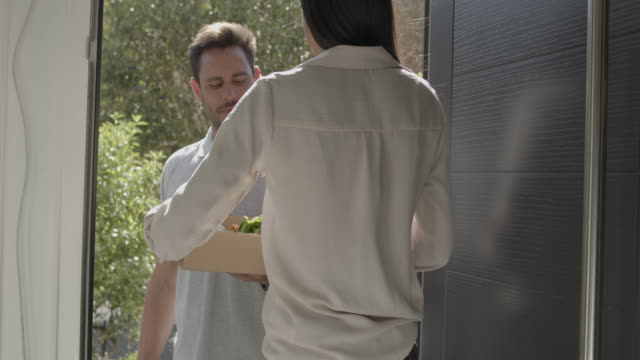 vidéos et rushes de female receiving package with vegetables at front door from delivery person - embrasure de porte