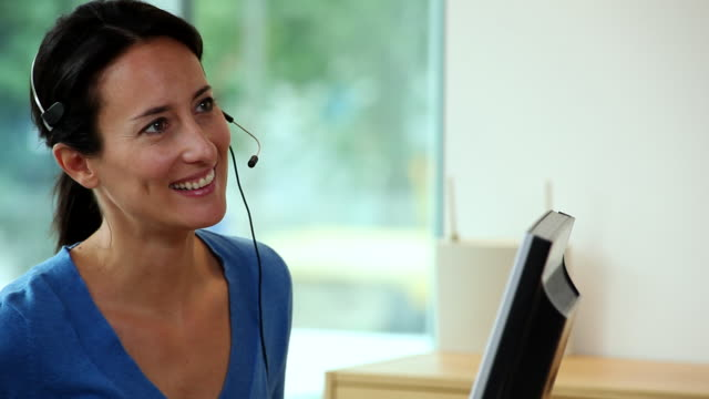 ms cu female receptionist looking at camera   / brussels , brabant, belgium - headset stock videos & royalty-free footage