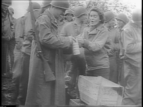 A female Red Cross worker and soldier wading through the mud to bring doughnuts to the soldiers then she hands them out with coffee / shots of...