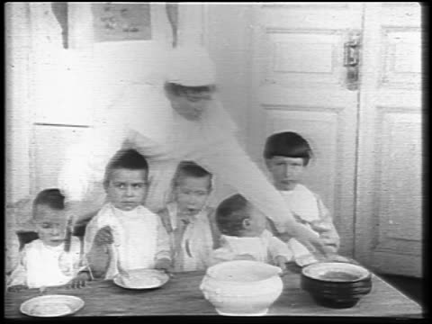 b/w 1921 female relief worker feeding group of children sitting at table indoors / russia / newsreel - 1921 stock videos & royalty-free footage