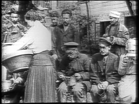b/w 1921 female relief worker giving food to seated famine victims outdoors / russia / newsreel - 1921 stock-videos und b-roll-filmmaterial