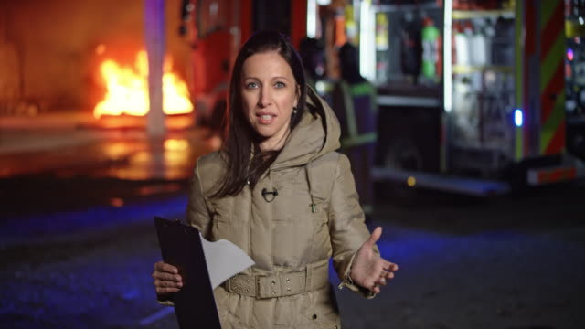 female reporter reporting from the scene of the fire seen in the background - journalist video stock e b–roll