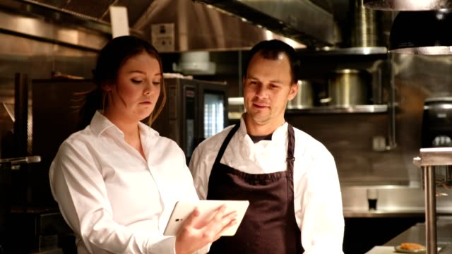 female restaurant manager discussed menu with chef - chef stock videos & royalty-free footage