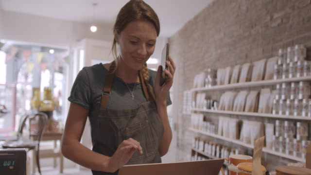 female retail store owner calling customer and looking on laptop computer in shop, using smart phone, wireless technology - retail occupation stock videos & royalty-free footage