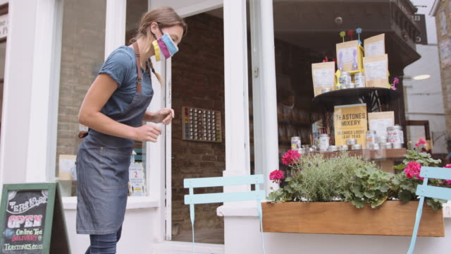 female retail store owner entrepreneur opening shop wearing protective face mask during coronavirus pandemic - safety stock videos & royalty-free footage