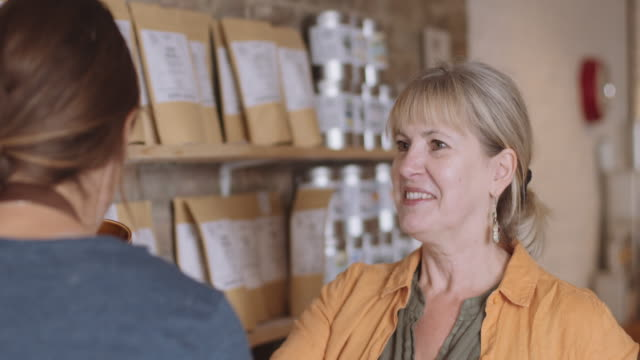 vidéos et rushes de female retail store owner talking to client and advising customer in shop smelling product - adulte d'âge mûr