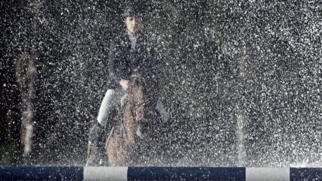 SLO MO Female rider and her horse jumping through a water curtain