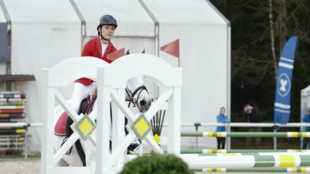 SLO MO DS Female rider jumping an obstacle on her white horse