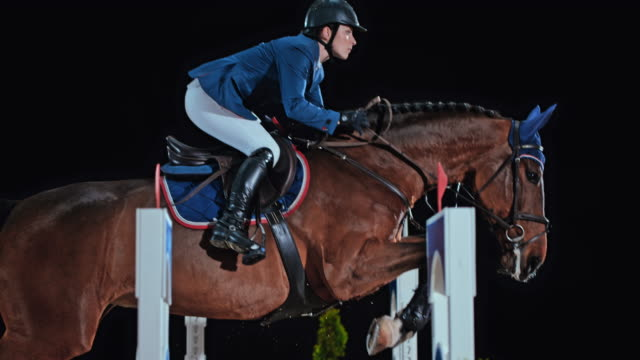 SLO MO Female rider jumping an oxer on her horse