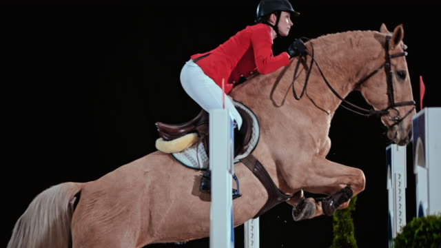 SLO MO Female rider jumping the oxer on her horse