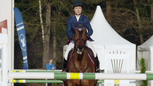 SLO MO Female rider on her horse jumping over an obstacle